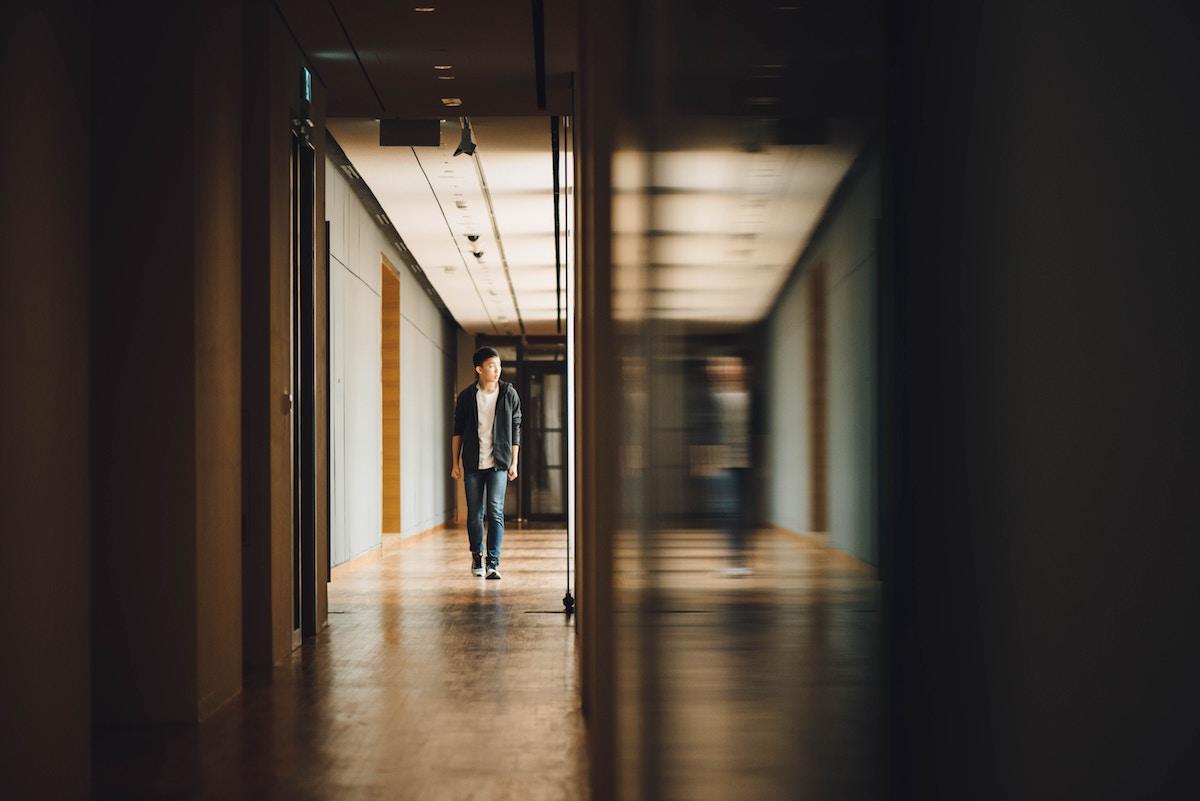 boy by himself in a school hallway
