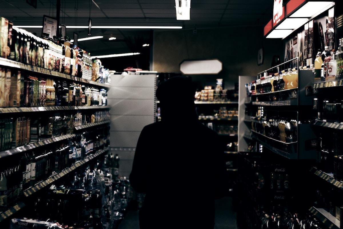 teen in hoodie in liquor store aisle