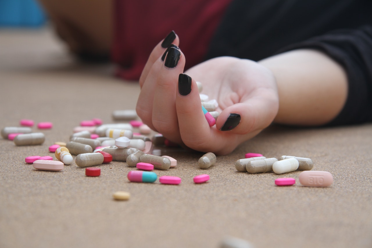 photo of girl on floor with pills in her hand