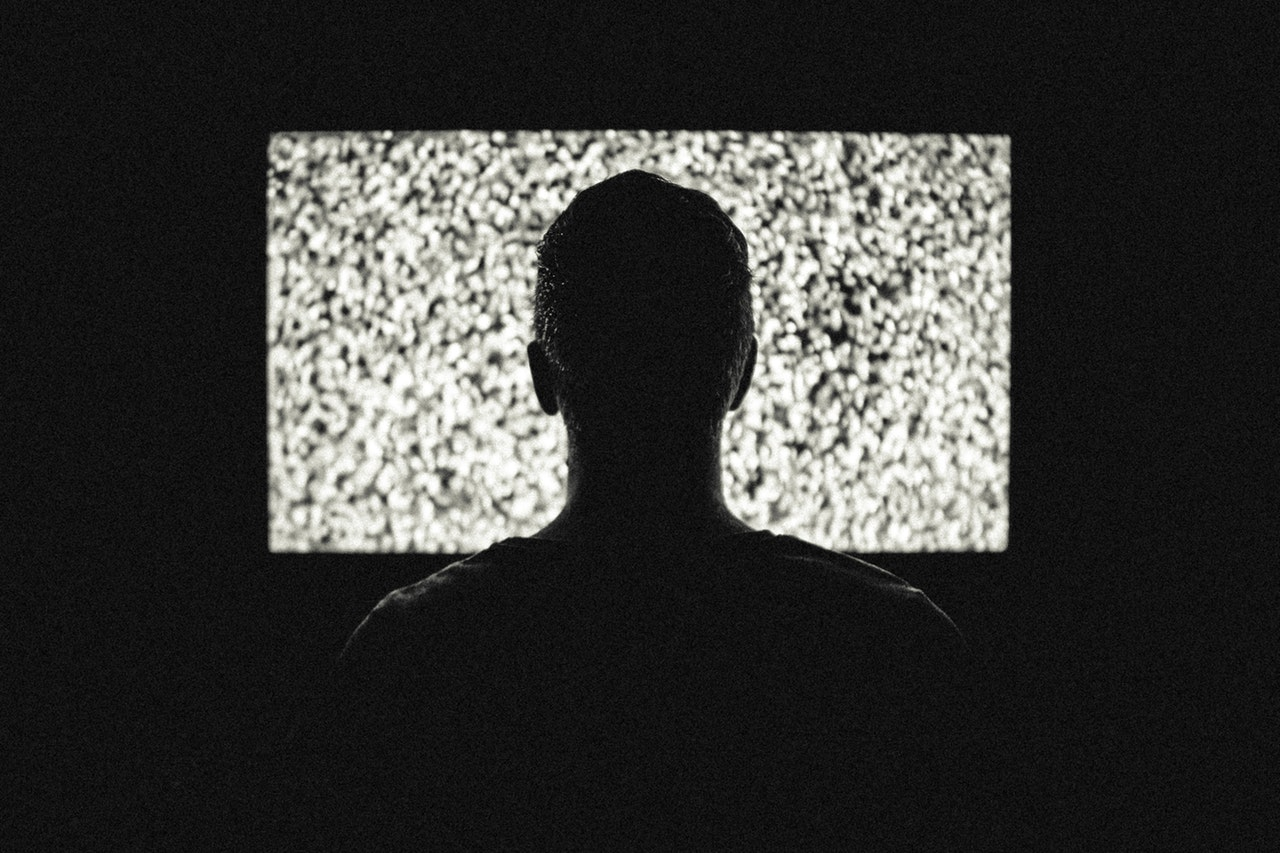 male in front of tv with static on screen