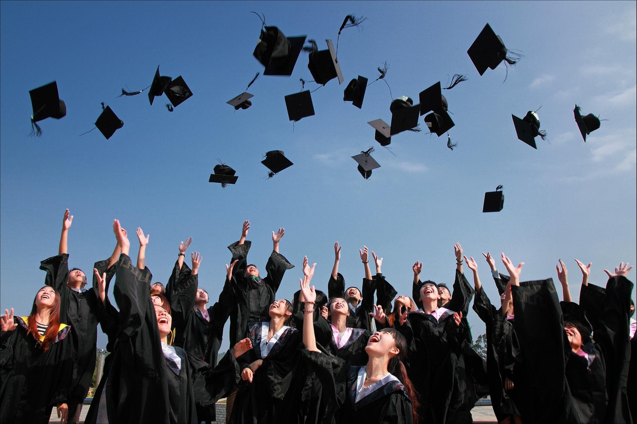 image of students throwing graduation caps student academic success