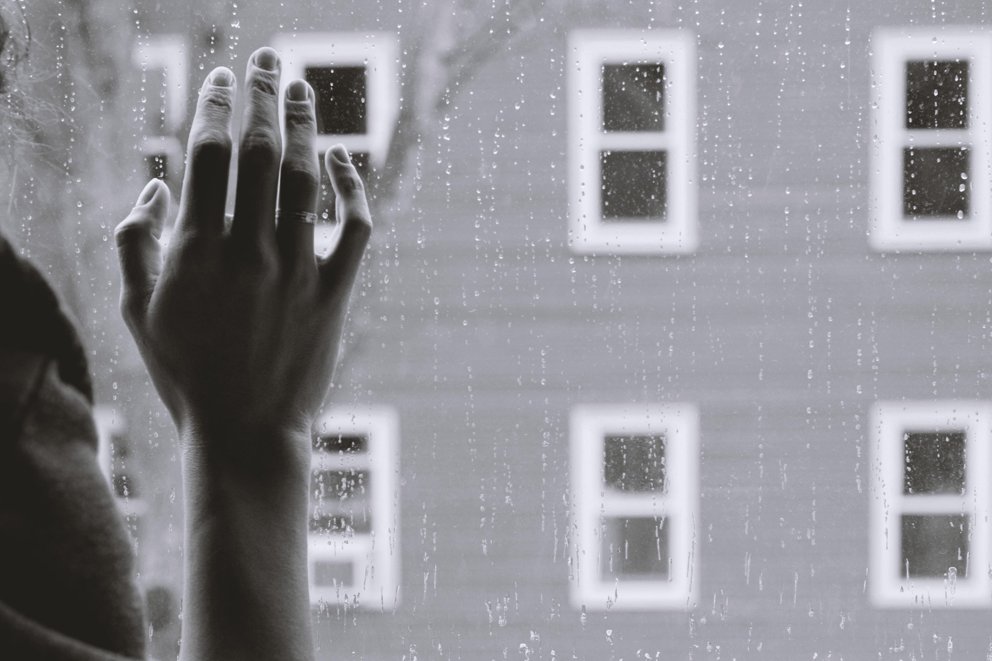 suicide teen hand on glass with rain falling down