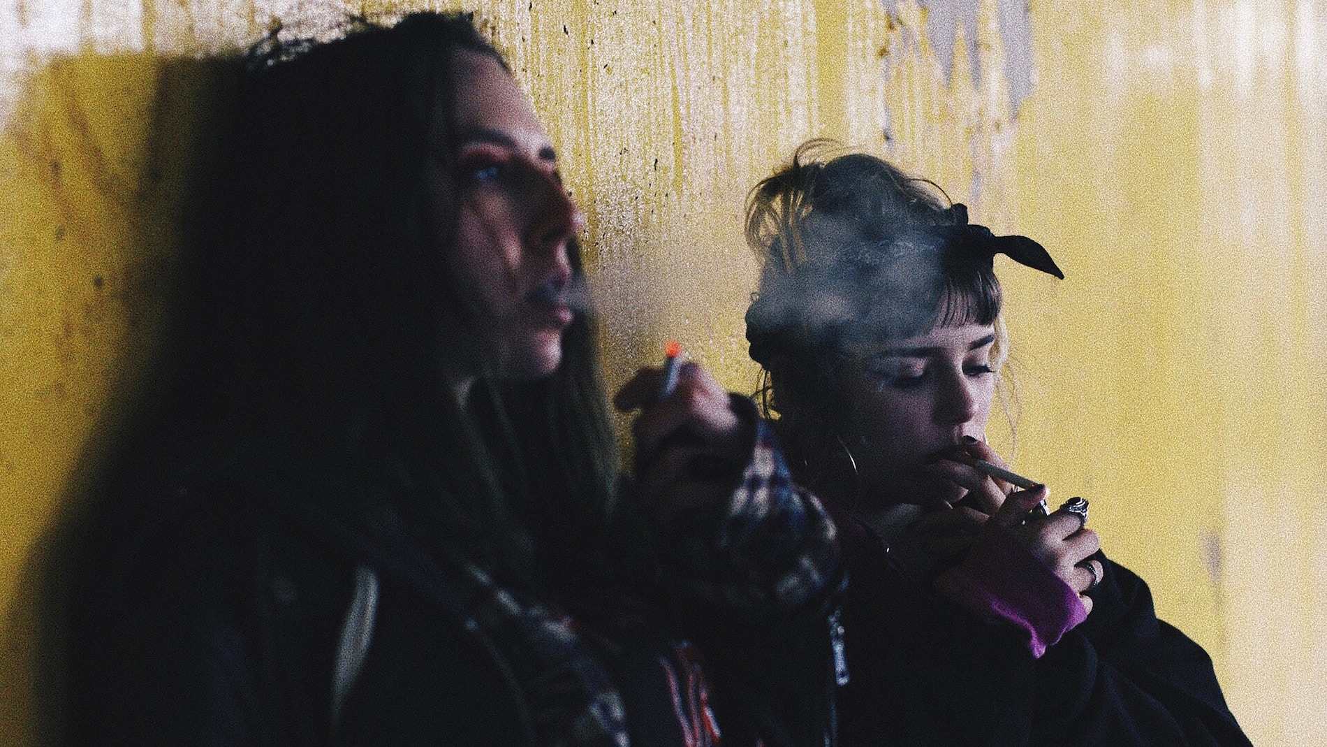 two teen girls smoking self harm up against a yellow wall